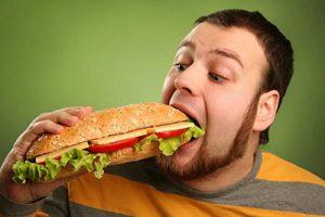 Мужчина ест сендвич